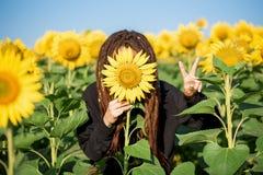 Ragazza di hippy con i dreadlocks divertendosi fra i girasoli fotografia stock libera da diritti