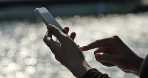 ragazza di 4k A che per mezzo di uno smartphone alla spiaggia, superficie dell'acqua frizzante stock footage