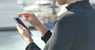 ragazza di 4k A che utilizza uno smartphone alla spiaggia, all'yacht & alla navigazione nel porto stock footage
