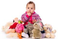 Ragazza di Lilltle con il lotto dei giocattoli Fotografia Stock