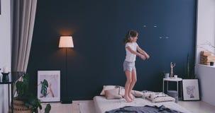 Ragazza di Litl che balla sul letto e che ascolta la musica con le cuffie senza fili Tempo libero e concetto moderno di stile di  archivi video