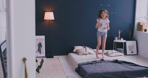 Ragazza di Litl che balla sul letto e che ascolta la musica con le cuffie senza fili Tempo libero e concetto moderno di stile di  video d archivio