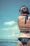Ragazza di lusso esile in un bikini nero sulla spiaggia Vista rara Perfezioni il corpo abbronzato, l'asino sexy, figura perfetta  fotografie stock libere da diritti