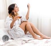 Ragazza di mattina a letto con l'orologio Fotografie Stock Libere da Diritti