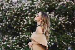 Ragazza di modello bionda alla moda e sensuale con il bello sorriso in cappotto senza maniche ed in occhiali da sole alla moda fotografia stock