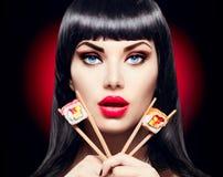 Ragazza di modello di bellezza che mangia i rotoli di sushi Fotografia Stock Libera da Diritti