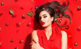Ragazza di modello sexy di bellezza che si trova sul fondo rosso con i fiori e le fragole rosa Bella giovane donna castana con ca fotografie stock libere da diritti