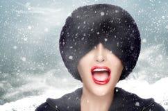 Ragazza di modo di inverno che Gesturing con il cappello di pelliccia che la copre occhi Immagini Stock