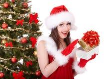 Ragazza di natale in cappello della Santa, albero di abete, contenitore di regalo. Fotografia Stock