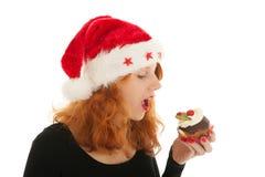 Ragazza di Natale che mangia dolce fotografia stock