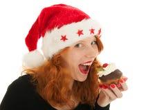 Ragazza di Natale che mangia dolce immagini stock