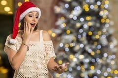 Ragazza di Natale che mostra palma vuota con il surprisi di sorriso dello spazio della copia fotografia stock libera da diritti