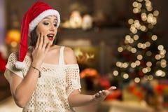 Ragazza di Natale che mostra palma vuota con il surprisi di sorriso dello spazio della copia fotografia stock