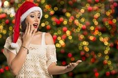 Ragazza di Natale che mostra palma vuota con il surprisi di sorriso dello spazio della copia immagine stock