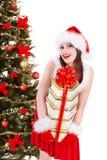Ragazza di Natale in contenitore di regalo della pila della tenuta del cappello di Santa. Immagini Stock