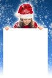 Ragazza di Natale felice che tiene insegna in bianco Immagine Stock