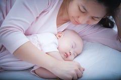 Ragazza di neonato che dorme in braccio della madre Immagini Stock