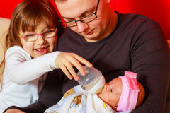 Ragazza di neonato d'alimentazione del padre con la bottiglia per il latte Fotografie Stock Libere da Diritti