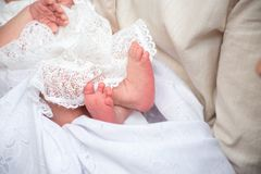 ragazza di neonato delle gambe nelle mani del genitore sui vestiti bianchi di un fondo immagini stock libere da diritti