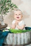 Ragazza di neonato di dieci mesi che si siede in un secchio di legno fotografia stock