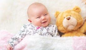 Ragazza di neonato sulla sua coperta con il suo orsacchiotto Immagini Stock