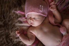 Ragazza di neonato sveglia della traversina in cappuccio rosa su lana Fotografie Stock Libere da Diritti