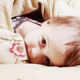Ragazza di ora di andare a letto che si trova sul letto nell'ambito delle coperture Fotografia Stock
