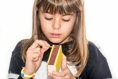 Ragazza di otto anni che gioca con le partite isolate su bianco Immagini Stock Libere da Diritti
