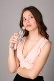Ragazza di pensiero con la bottiglia di acqua Fine in su Fondo grigio Immagini Stock