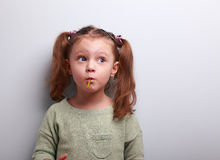Ragazza di pensiero divertente del bambino che mangia lecca-lecca e cercare Immagini Stock Libere da Diritti
