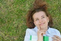 Ragazza di pensiero sveglia con il libro che si trova sull'erba nel parco Fotografia Stock