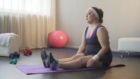 Ragazza di peso eccessivo che prova a fare gli esercizi di sport per essere sano ed a dimagrire, allenamento stock footage