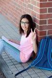 Ragazza di Preteenager con lo zaino che si siede sul pavimento Fotografie Stock Libere da Diritti