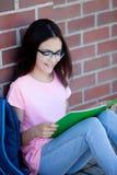 Ragazza di Preteenager con lo zaino che si siede sul pavimento Immagini Stock