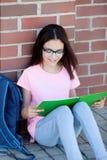 Ragazza di Preteenager con lo zaino che si siede sul pavimento Fotografie Stock