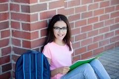 Ragazza di Preteenager con lo zaino che si siede sul pavimento Fotografia Stock Libera da Diritti