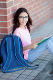 Ragazza di Preteenager con lo zaino che si siede sul pavimento Immagini Stock Libere da Diritti