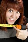 Ragazza di Redhead che per mezzo dello strumento di nastro di misurazione fotografia stock