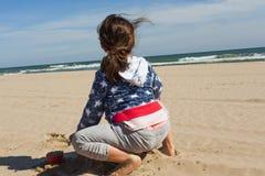 Ragazza di retrovisione che gioca con la sabbia nella spiaggia in un giorno ventoso Immagini Stock Libere da Diritti