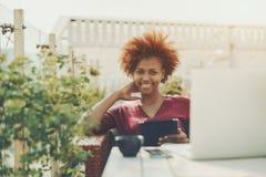 Ragazza di risata biraziale che lavora al computer portatile in caffè della via Immagini Stock Libere da Diritti