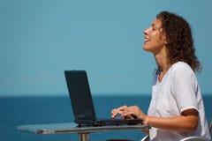Ragazza di risata con il computer portatile. Si siede alla tabella sulla spiaggia immagine stock