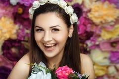 Ragazza di risata con la fine graziosa del fondo del fiore del fronte su Fotografie Stock Libere da Diritti