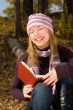 Ragazza di risata con un libro Fotografie Stock Libere da Diritti