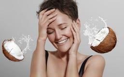 Ragazza di risata felice su un fondo grigio con una diffusione della noce di cocco Fotografia Stock