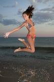 Ragazza di salto sulla spiaggia Fotografie Stock