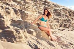 Ragazza di Sanny in costume da bagno su un fondo della sabbia Immagini Stock Libere da Diritti