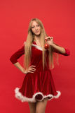 Ragazza di Santa che posa su un fondo rosso con il giocattolo Fotografia Stock Libera da Diritti