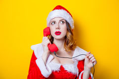Ragazza di Santa Clous in vestiti rossi con il microtelefono fotografia stock
