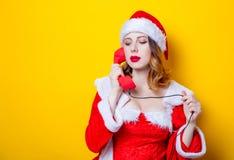 Ragazza di Santa Clous in vestiti rossi con il microtelefono fotografia stock libera da diritti