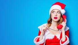 Ragazza di Santa Clous in vestiti rossi con il microtelefono immagini stock